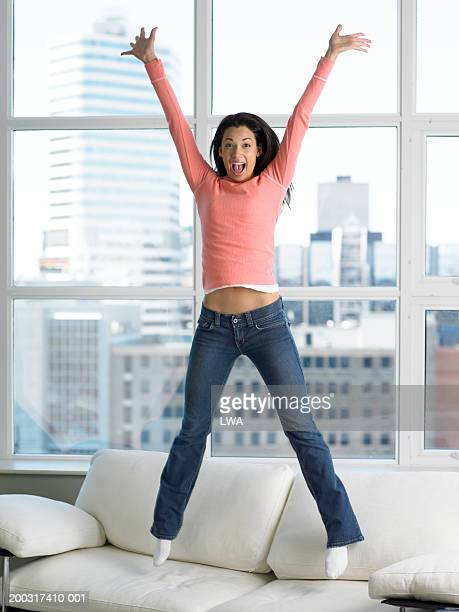 Woman jumping on sofa with arms outstretched smiling, portrait