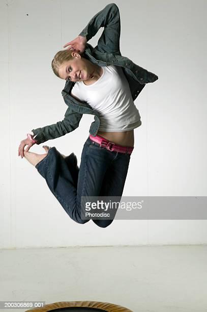 Woman jumping on trampoline in studio