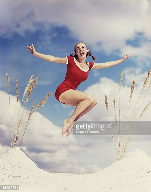 Woman Jumping on White Sand