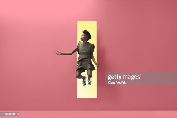 Woman jumping out of rectangular opening of coloured wall