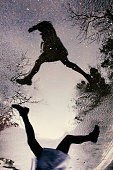 Woman jumping over a water puddle