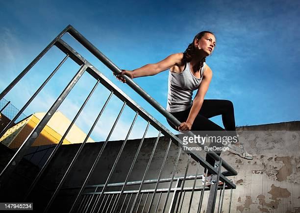 Woman jumping over fence obstacles
