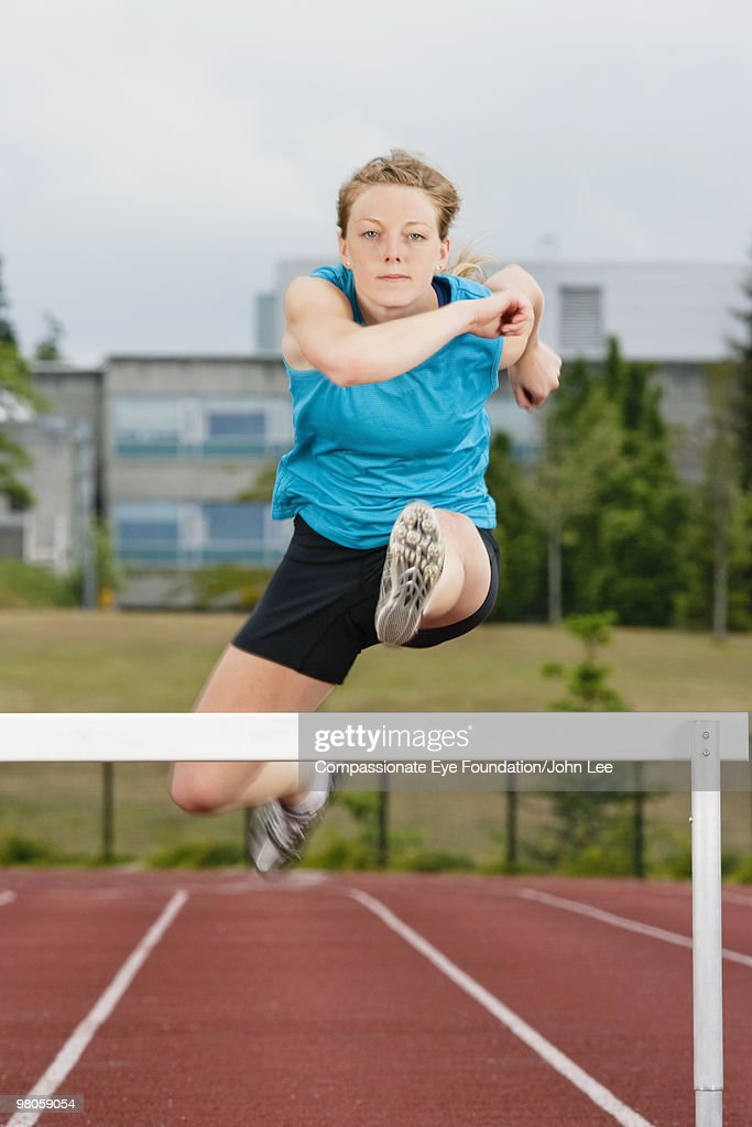woman jumping over hurdle on running track : Stock Photo