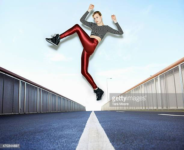 woman jumping over road