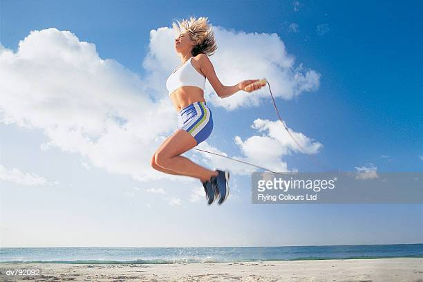 Woman Jumping Rope on the Beach
