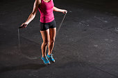 Cropped view of young fit woman (20s) in gym working out with jump rope.