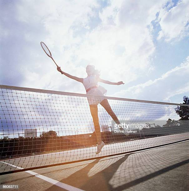 Woman jumping while playing tennis