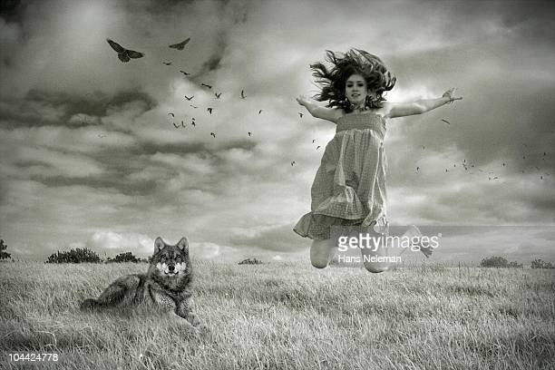Woman jumping with a wolf sitting near her, Republic of Ireland