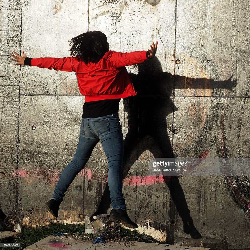 Woman Jumping With Arms Outstretched Against Wall