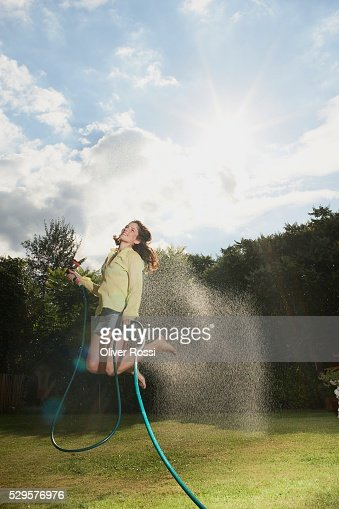 Woman Jumping with Garden Hose : Stock Photo