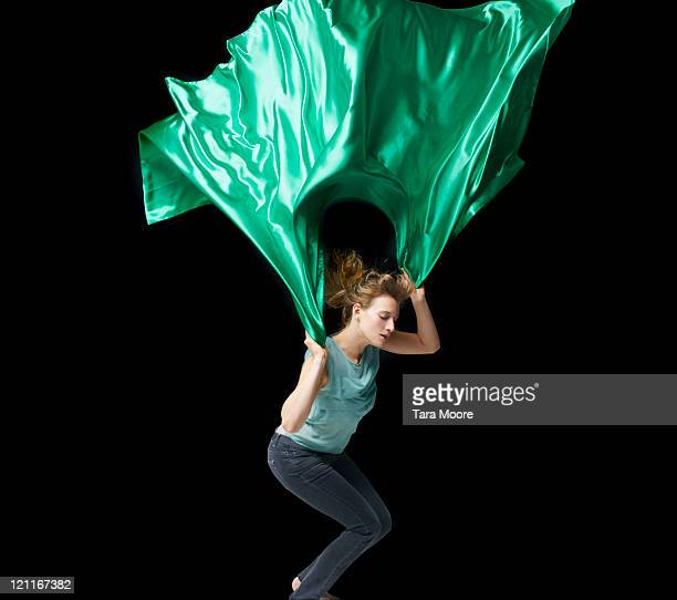 woman jumping with green material