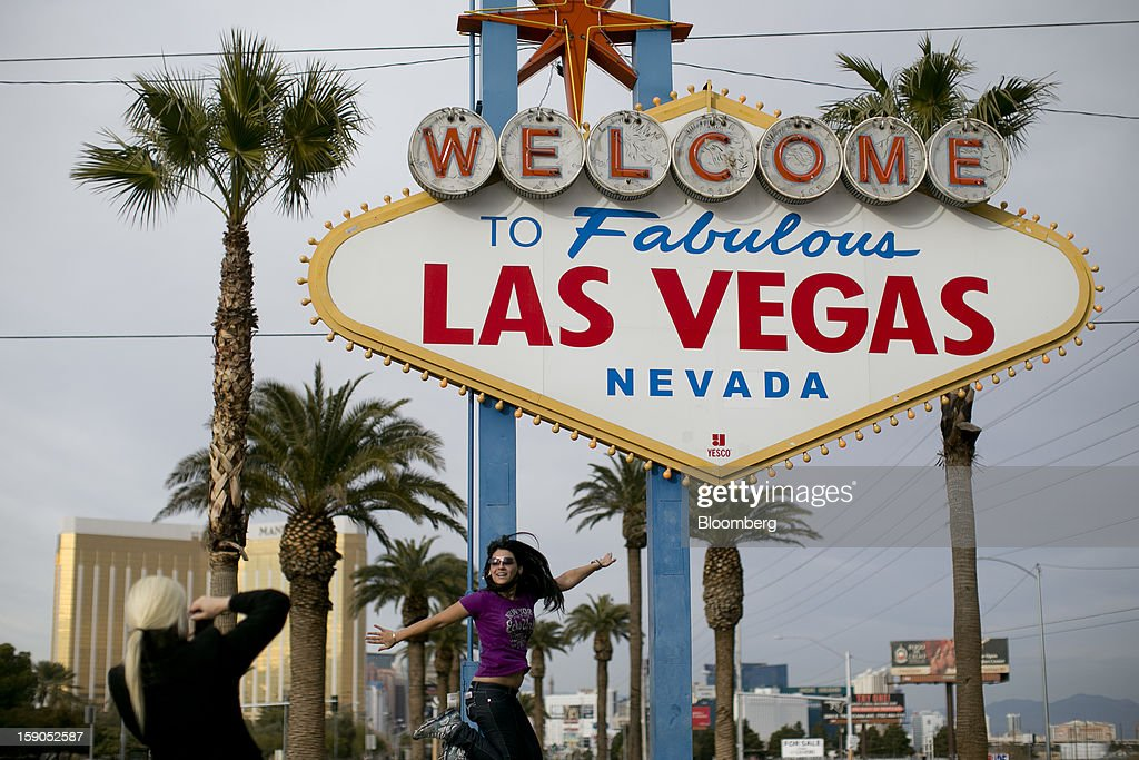 A woman jumps as she is photographed in front of the 'Welcome to Fabulous Las Vegas' sign along the Strip in Las Vegas, Nevada, U.S., on Sunday, Jan. 6, 2012. The 2013 International Consumer Electronics Show trade show, which runs until Jan. 11, is the world's largest annual innovation event that offers an array of entrepreneur focused exhibits, events and conference sessions for technology entrepreneurs. Photographer: Andrew Harrer/Bloomberg via Getty Images