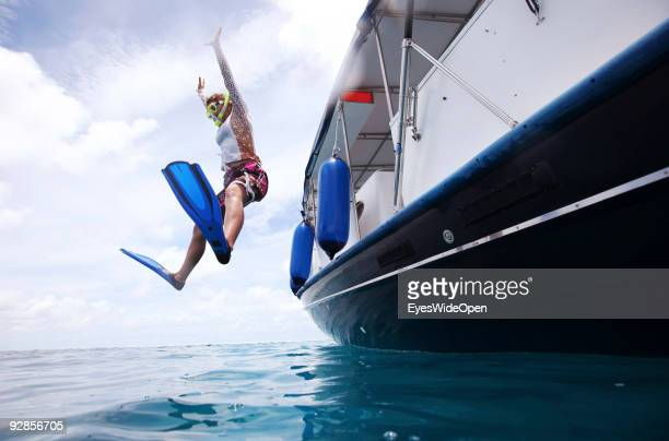 Woman jumps from a diving boat on a snorkeling trip to the reef of Addu Atoll on September 27 2009 in Male MaldivesThe maldive islands consist of...