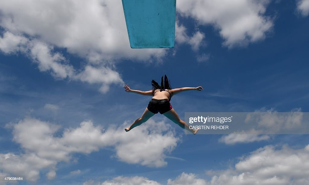 A woman jumps from a diving platform into the water of the public openair swimming pool in Neumuenster northern Germany on June 30 2015...