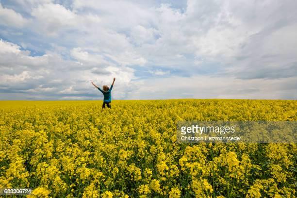 Woman jumps in canola field