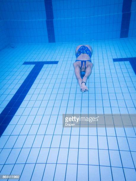 Woman jumps in the pool and dives