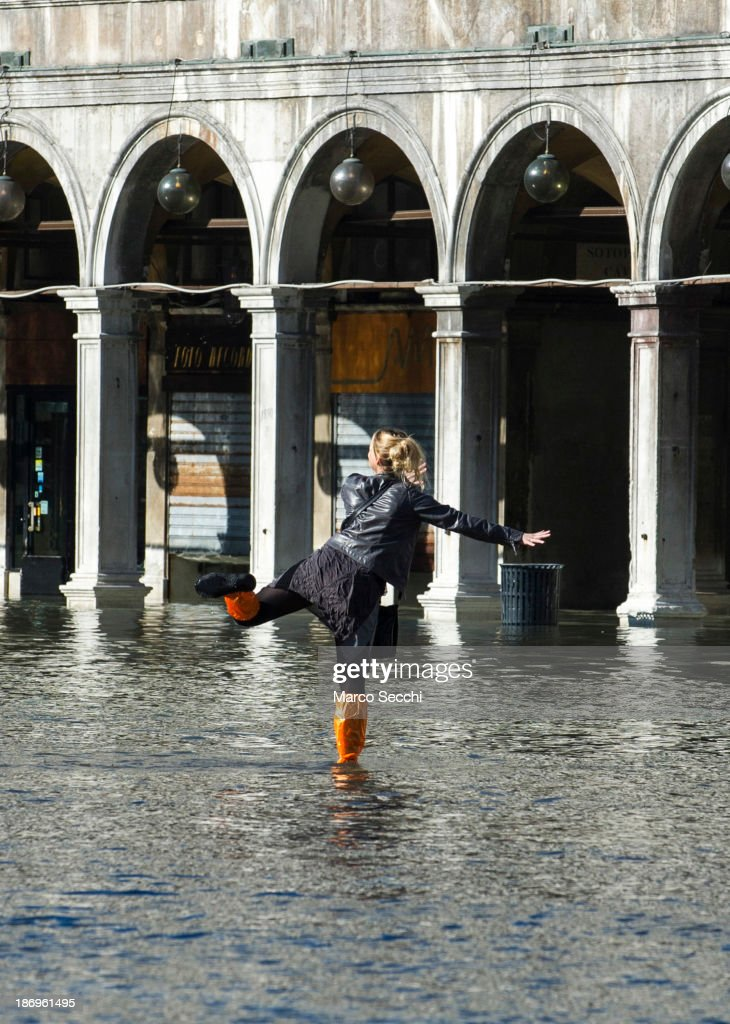 A woman jumps in the water in Saint Mark's Square during today's Acqua Alta on November 5, 2013 in Venice, Italy. The high tide, or acqua alta as it is locally known, is a natural event most commonly affecting the city during Autumn and Winter.