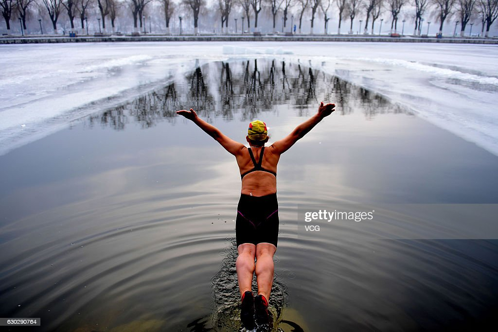 A woman jumps into a pool dug in the frozen river at Beiling Park in the smog on December 20, 2016 in Shenyang, Liaoning Province of China. Winter swimmers exercised in the smog in Shenyang. At least 24 cities in North China issued red alerts on Dec 16 as heavy smog will shroud the country's northern regions in the following days.