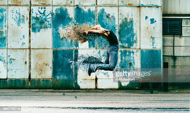 Woman jumps into the air and her body dissolves