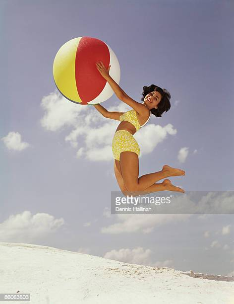 Woman Jumps While Holding Colorful Beach Ball