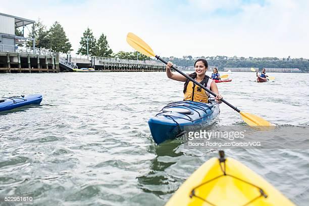 Woman kayaking in urban harbor