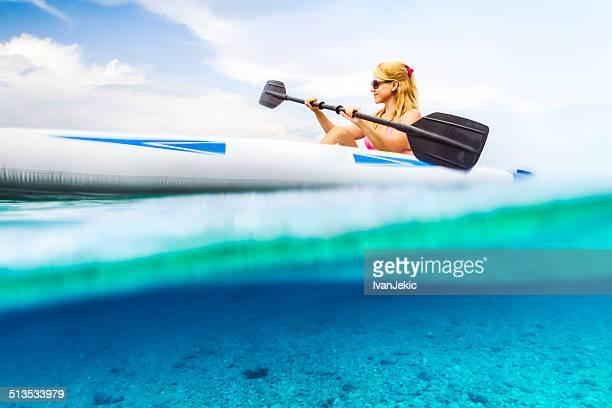 Woman kayaking on the blue sea.