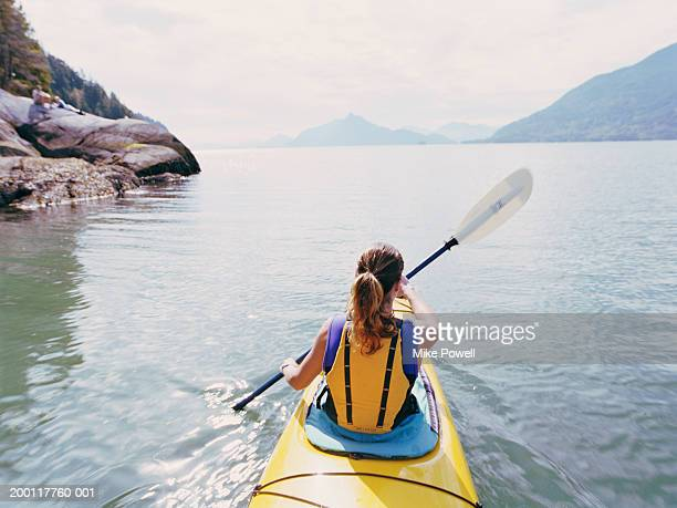 Woman kayaking, swinging paddle in air, rear view