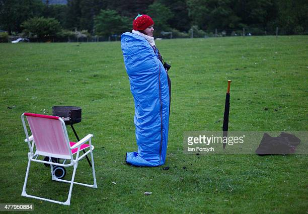 A woman keeps warm by standing in her sleeping bag at sunrise at the ancient stone circle at Castlerigg as she celebrates the summer solstice on June...