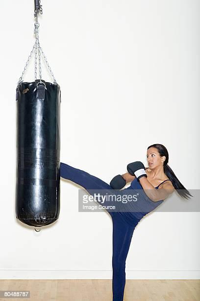 A woman kicking a punch bag