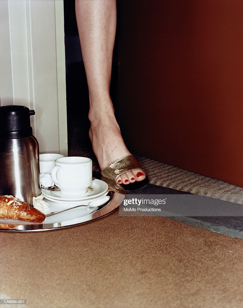 Woman kicking breakfast tray out of room, low section : Stock Photo