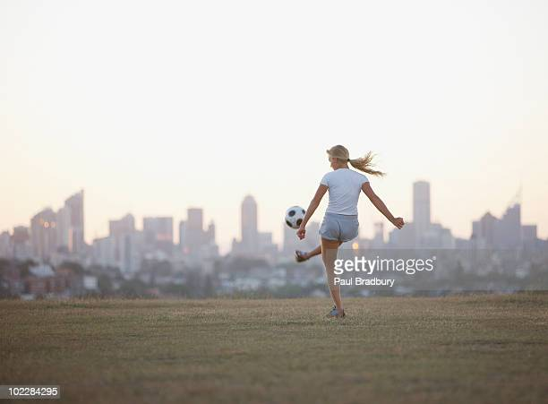 Woman kicking soccer ball in urban park