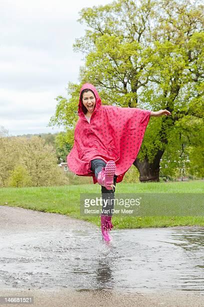 Woman kicking water in puddle in rain.