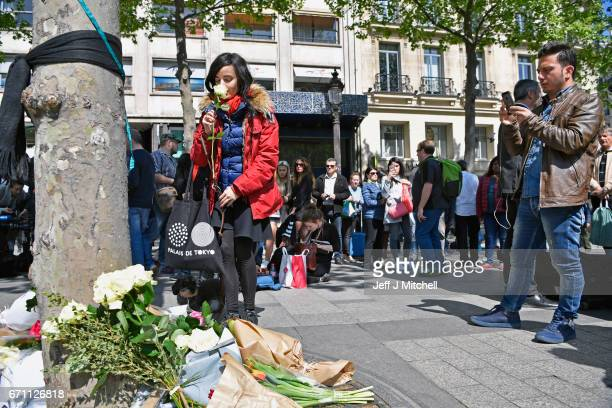 A woman kisses a flower near the Marks and Spencer on the Champs Elysees in Paris following yesterday's shooting of a police officer on April 21 2017...