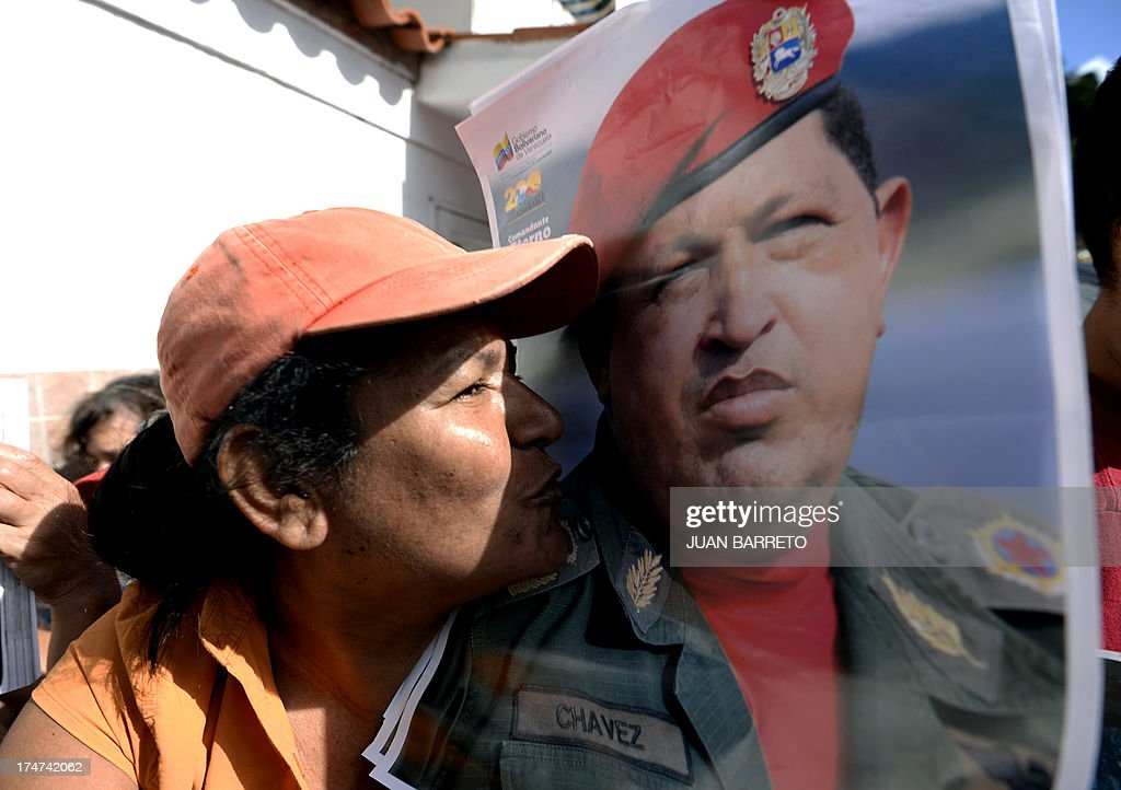A woman kisses a picture of the late President Hugo Chavez, during a ceremony to commemorate his birthday anniversary, in Caracas, on July 28, 2013. AFP PHOTO/Juan Barreto