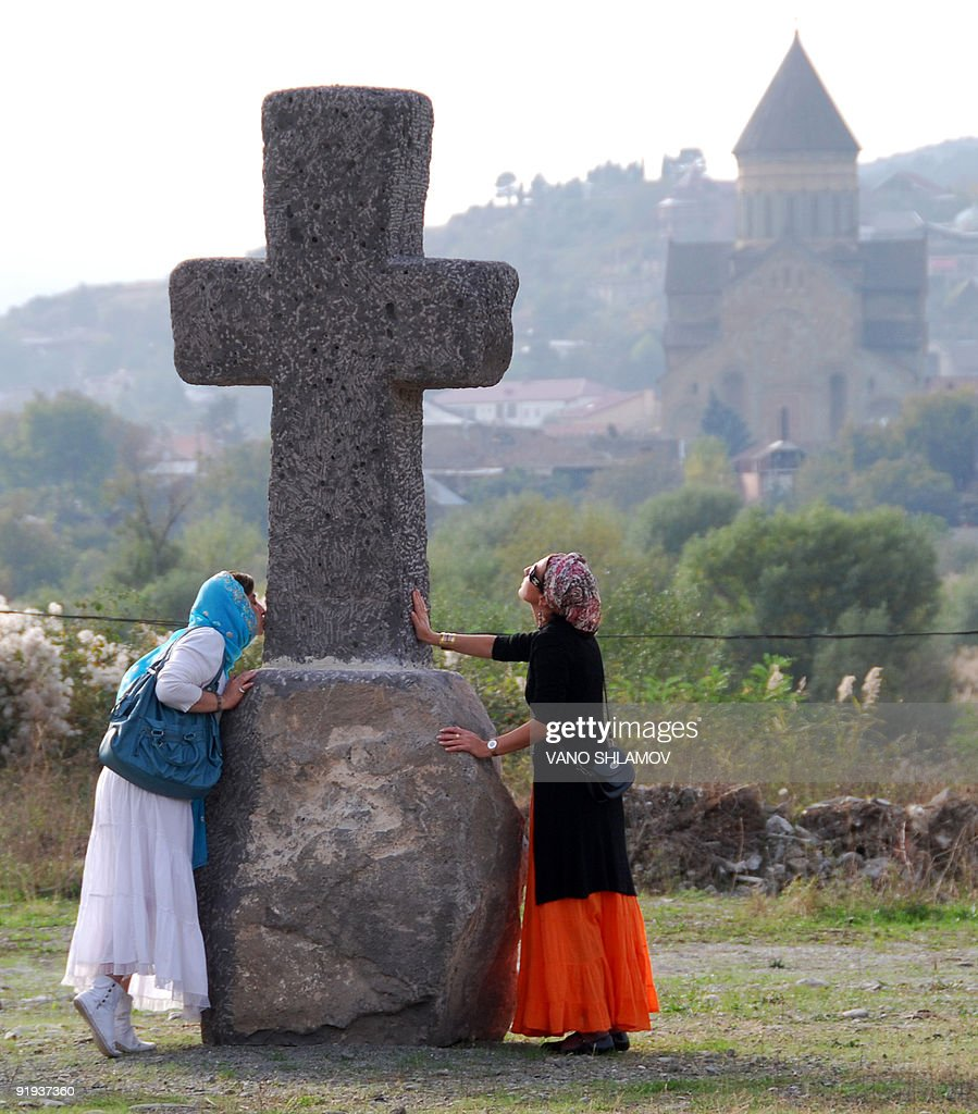 A woman kisses an ancien cross during the Mtskhetoba celebration in honor of the Orthodox monastery in Mtskheta, some 20 kms outside Tbilisi, on October 14, 2009.