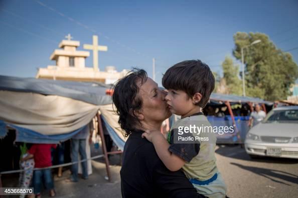 ANKAWA ERBIL KURDISTAN IRAQ A woman kisses her son outside the Mar Tshmony church 500 Christian families have been sheltered at Mar Tshmony church...