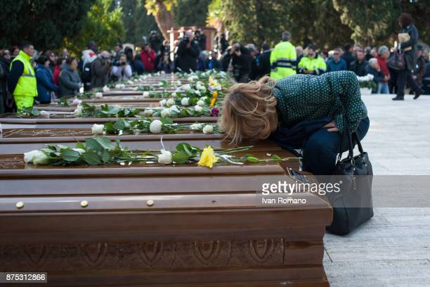 A woman kisses one of the bars of the migrant women in the Monumental Cemetery of Salerno on November 17 2017 in Salerno Italy A funeral was held for...