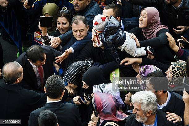 A woman kisses the hand of Turkish President Recep Tayyip Erdogan in front of a polling station in Istanbul on November 1 2015 Turkey voted November...