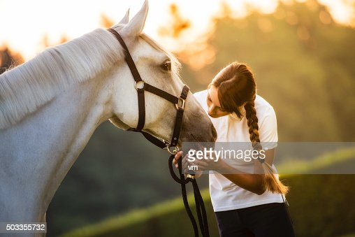 Woman kissing a horse on the head in nature