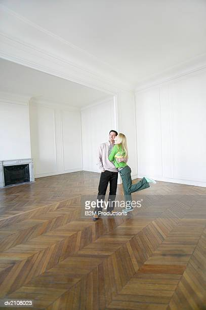 Woman Kissing a Man's Cheek in a Large Empty Room