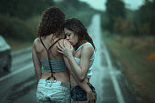 Young women couple have hugs on the road in the rain