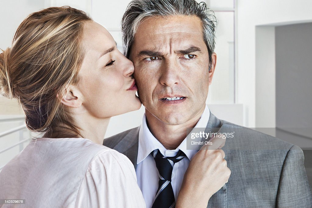 Woman kissing angry or concerned man on cheek : Stock Photo