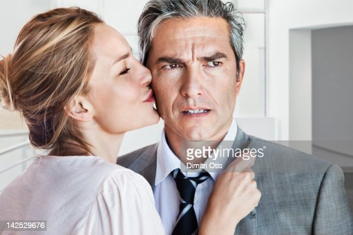 Woman kissing angry or concerned man on cheek : Photo