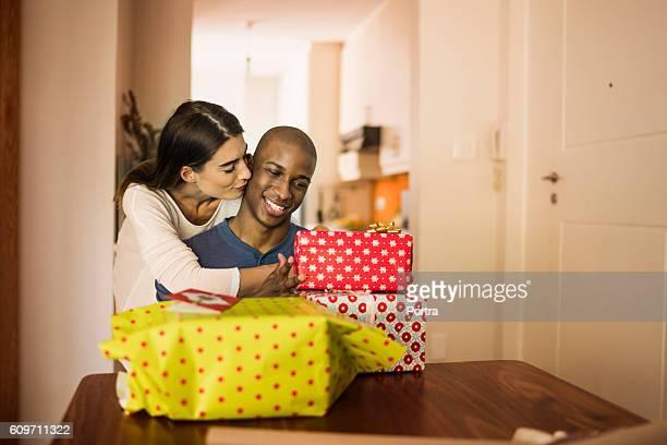 Woman kissing boyfriend by Christmas presents