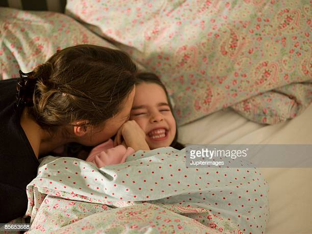 Woman kissing daughter in bed