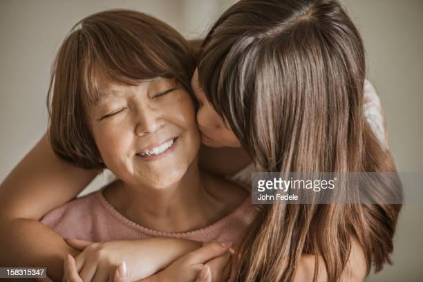 Woman kissing grandmother