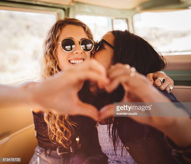 Woman kissing her girl friend on cheek with hand heart