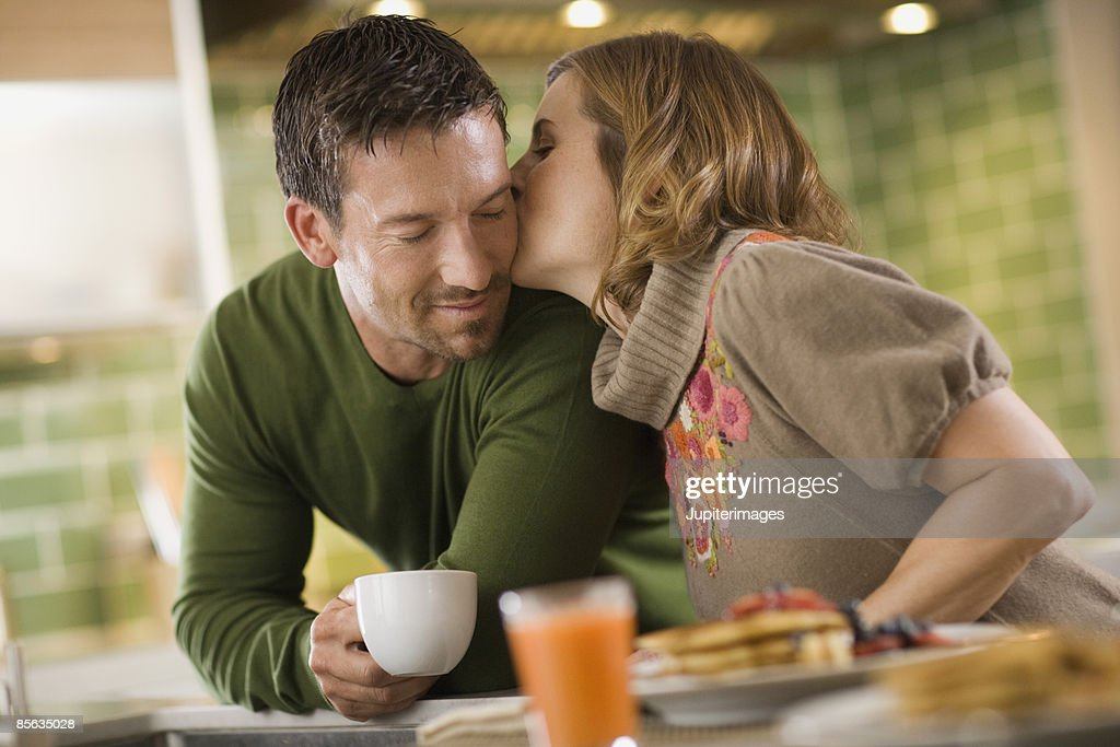 Woman kissing man at breakfast : Stock Photo