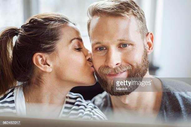 Woman kissing mans cheek at home