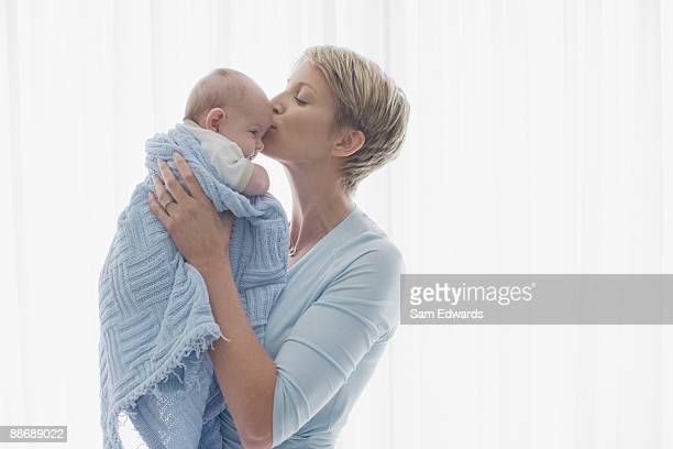 Woman kissing newborn baby